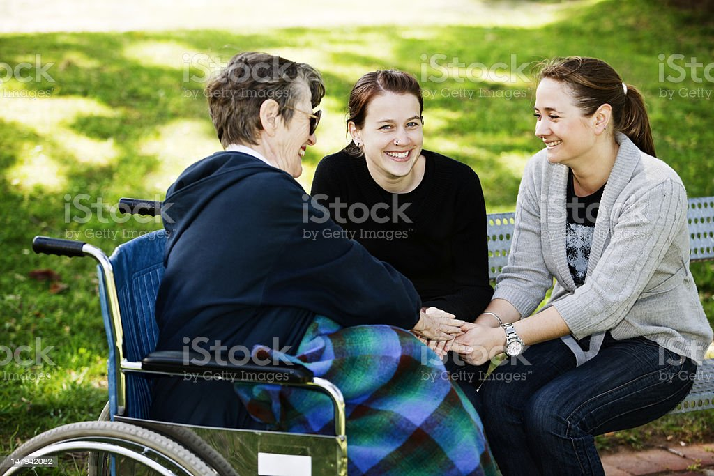 Wheelchair bound old woman and two young women clasp hands royalty-free stock photo