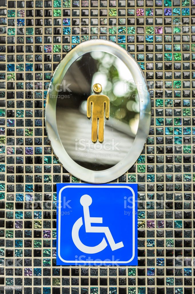 Wheelchair gentleman toilet signs on black square mosaic wall stock photo