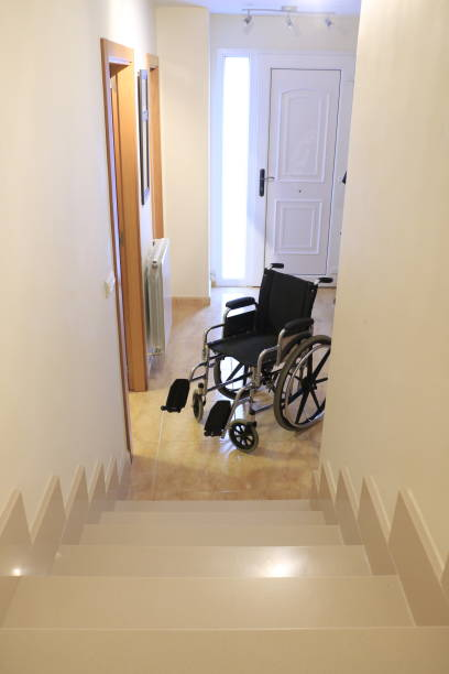 A wheelchair in front of a staircase in a house stock photo