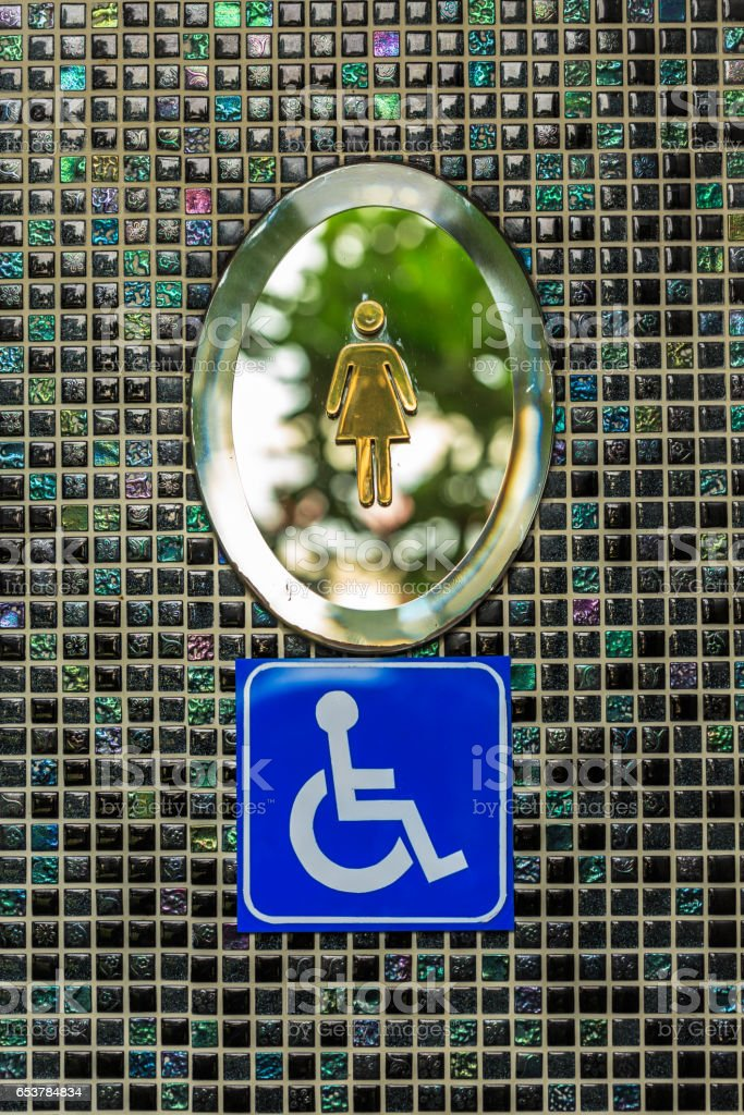 Wheelchair lady toilet signs on black square mosaic wall stock photo