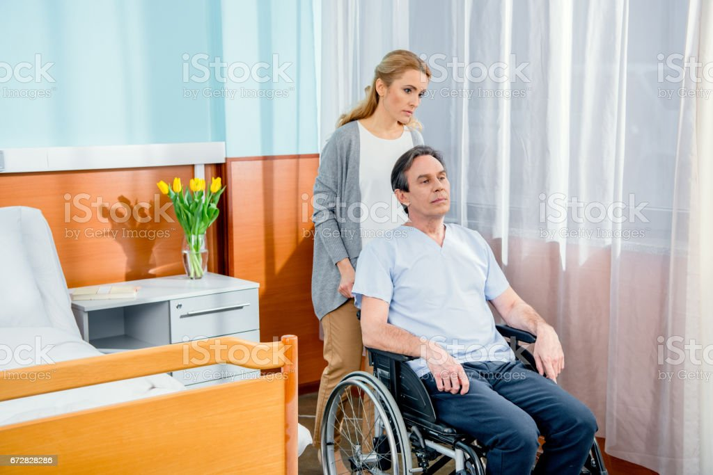 wheelchair man with wife near by in hospital chamber stock photo
