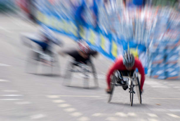 wheelchair marathon racers during race, motion blur - wheelchair sports stock photos and pictures