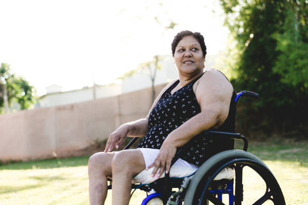 Wheelchair mature woman at public park stock photo