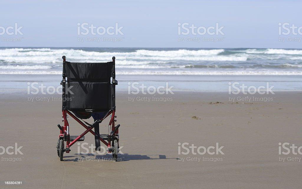 Wheelchair on the Beach stock photo