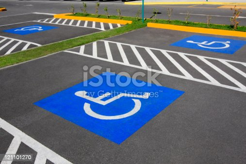 Handicap parking space. Parking lot inaugurated recently. Universal symbols painted on the asphalt.