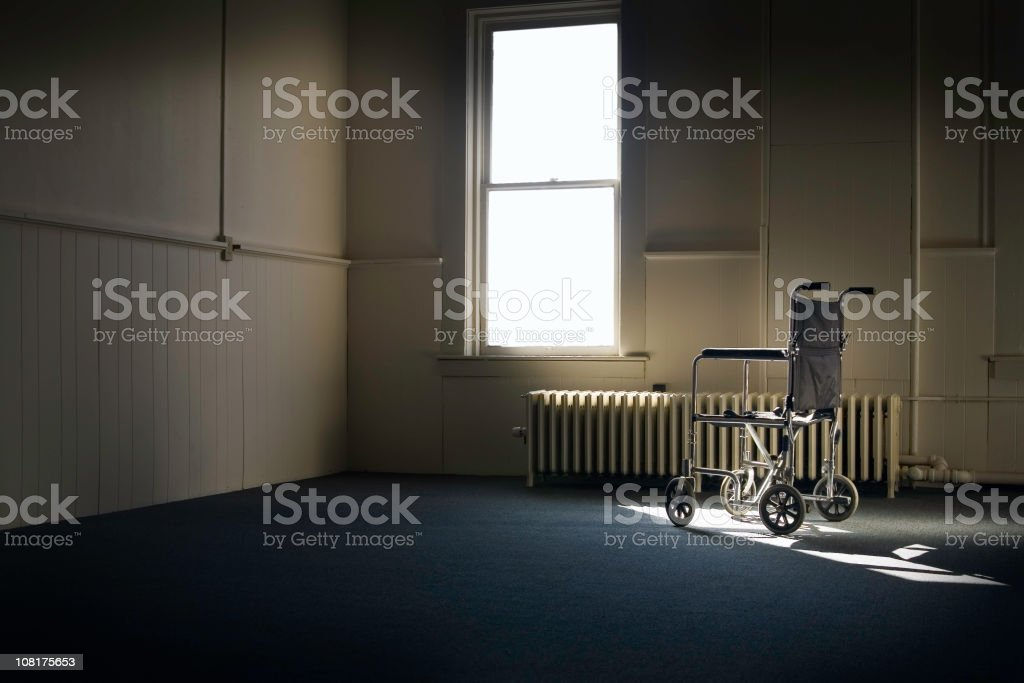 Wheelchair Sitting in Empty Room By Window stock photo