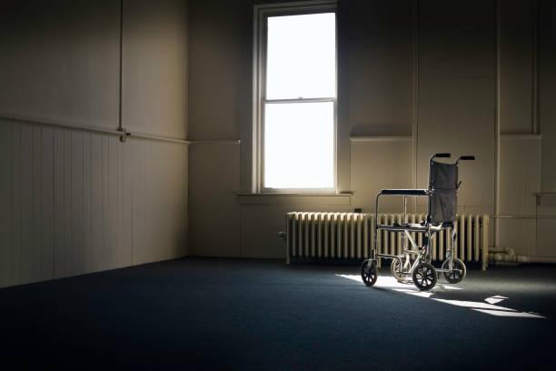 salon en fauteuil roulant dans la salle vide par la fenêtre - hopital psychiatrique photos et images de collection