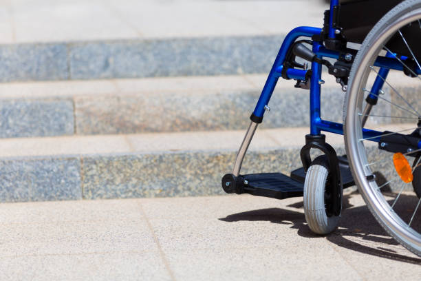 wheelchair standing before inaccesible steps stock photo