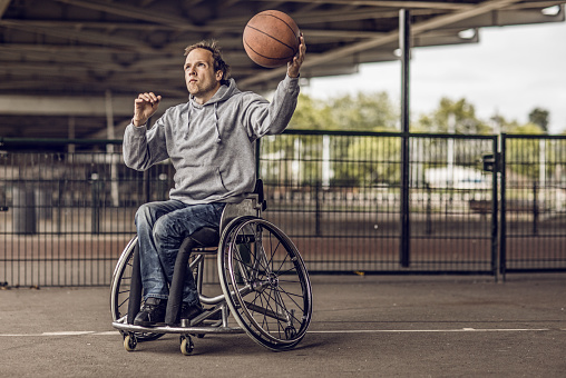 istock Wheelchair using young man during an outdoor urban basketball training session 995288994