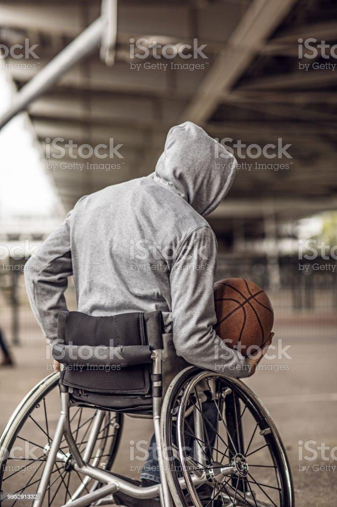 Silla de ruedas con la joven durante una sesión de entrenamiento de baloncesto urbano al aire libre - foto de stock