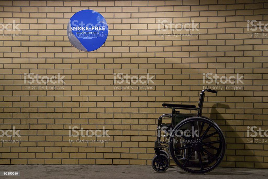 Wheelchair with No Smoking Sign royalty-free stock photo
