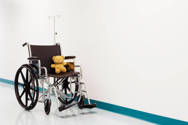 Wheelchair with teddy bear in hospital corridor Wheelchair with teddy bear in hospital corridor teddy bear stock pictures, royalty-free photos & images