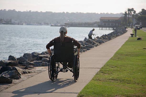 Wheelchair woman on sidewalk image stock photo