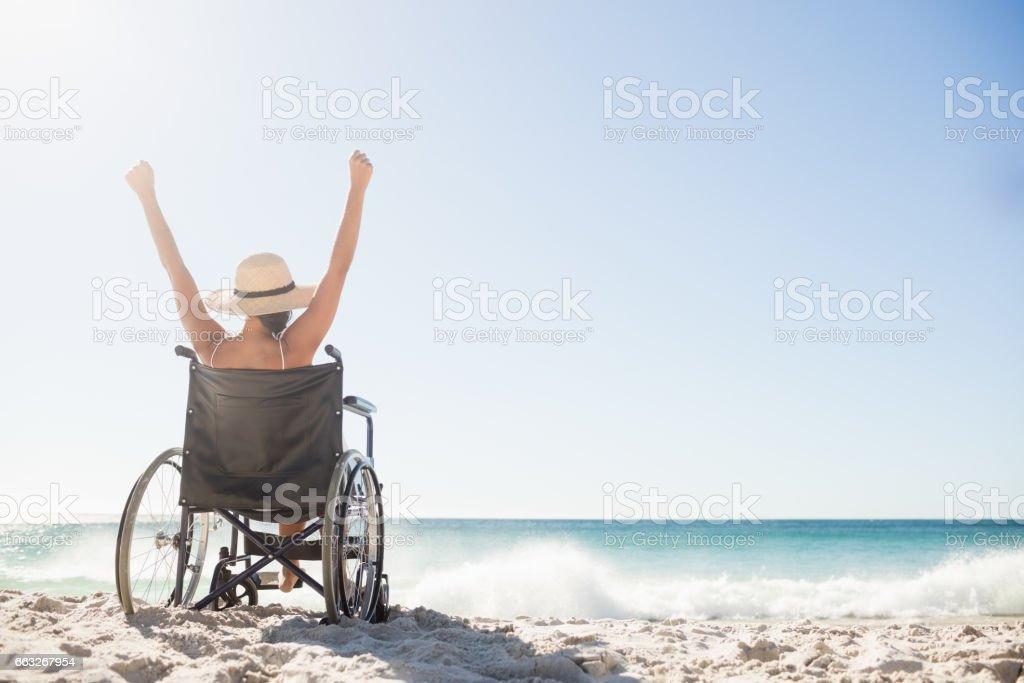 Mujer de silla de ruedas, sentado con los brazos - foto de stock