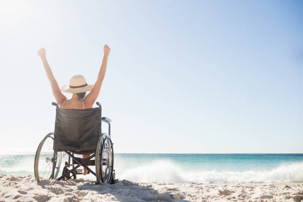 wheelchair woman sitting  with arms up - sedia a rotelle foto e immagini stock