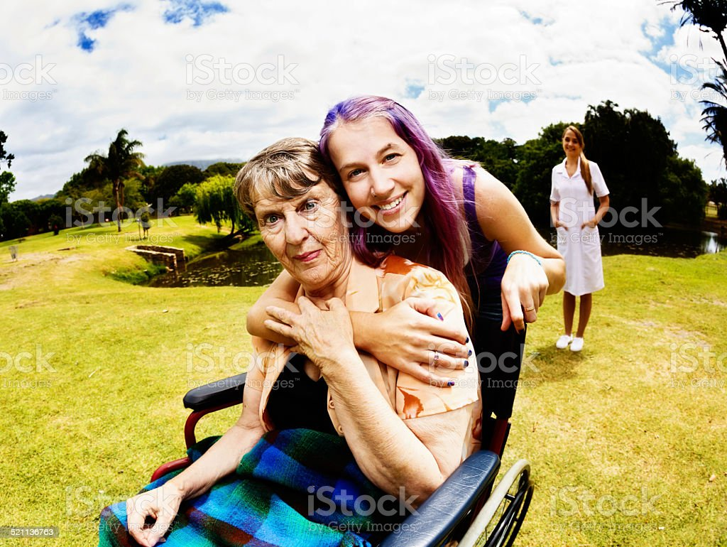 Wheelchair-bound grandmother with affectionate young relative, caregiver in background stock photo