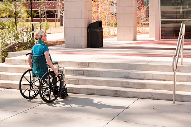 Wheelchair-bound woman faces inaccessible stairs. Civil rights. stock photo