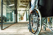 Paralyzed man in a wheelchair on the move in the disabled office building.