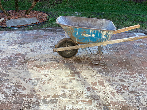 Boynton Beach, United States, December 14, 2020: A wheel barrel was used to bring in sand to fill the cracks between the brick pavers on a newly installed patio in the backyard of a home. The sand will then be compacted into the spaced between the pavers.