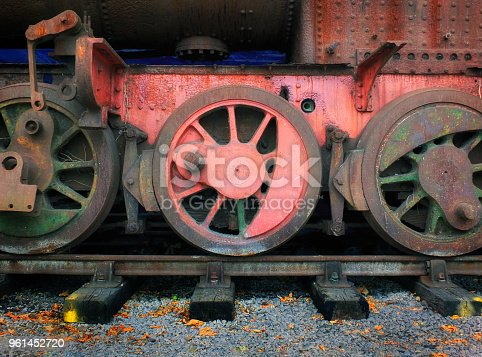 Wheels of an abandoned vintage rusty steam engine with rust red paint and tracks