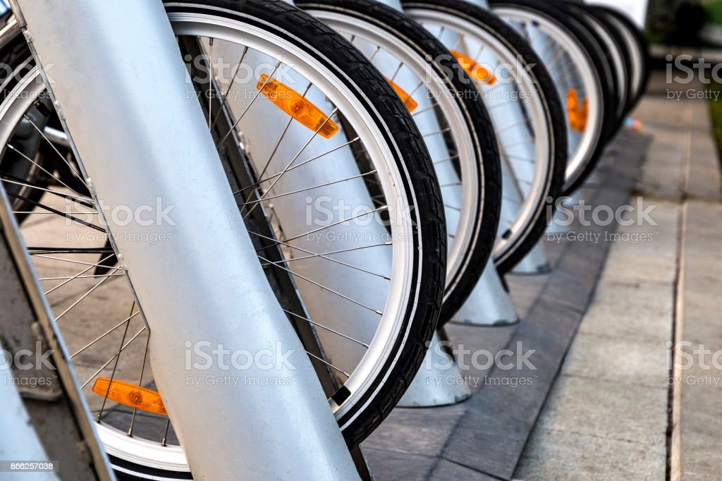 wheels of bicycle for rent standing on the parking stock photo