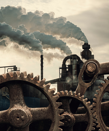 Rusted wheels of industry spin.  Composite image.