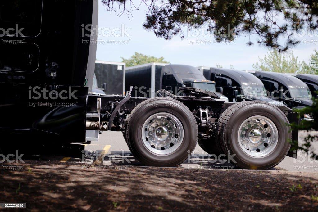 Wheels with tires of black big rig semi truck with five wheel on wheels with tires of black big rig semi truck with five wheel on background of semi publicscrutiny Images