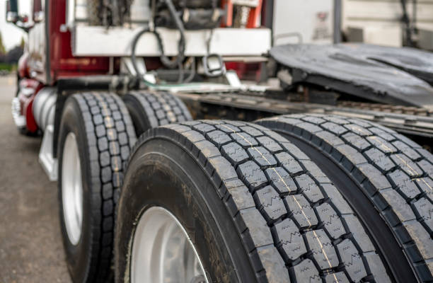 Wheels with tires on axels of big rig semi truck standing on parking lot stock photo