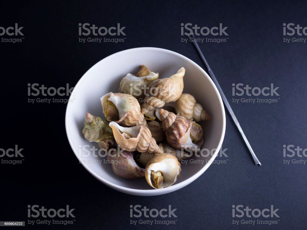 Whelks in bowl on black background stock photo
