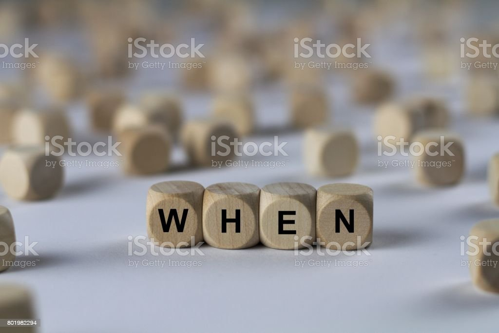 when - cube with letters, sign with wooden cubes stock photo