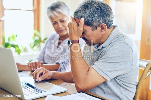 Shot of a mature couple looking stressed out while managing their paperwork together at home