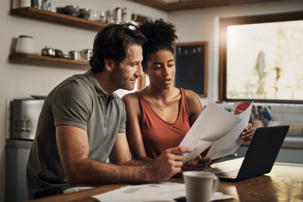 When did this happen? Cropped shot of an affectionate young couple going through paperwork while doing their budget at home husband stock pictures, royalty-free photos & images
