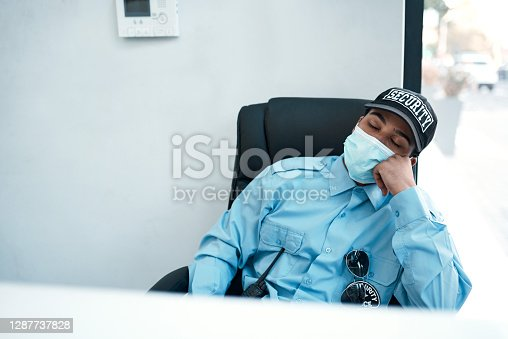 Shot of a masked young security guard sleeping at a desk in an office