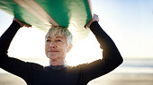 Cropped shot of a senior woman holding a surfboard on top of her head on her way to go surfing