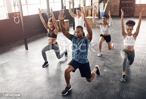 Shot of a group of young people doing lunges together during their workout in a gym