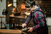 Hardworking Girl Dressed In Protective Coveralls And Protective Glasses Welding Metal Plate In Workshop