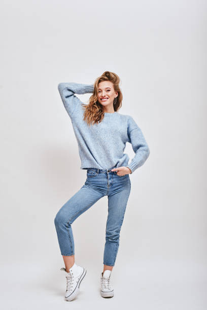 When life feels playful. Brown-haired, cute girl posing in studio, fixing her hair and smiling at camera isolated over white background Full-length portrait of playful, vivacious girl wearing blue sweater, jeans, converse, fixing her hair, while smiling happily at camera, isolated over white background. nude women pics stock pictures, royalty-free photos & images