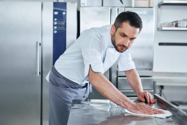 ao preparar alimentos mantê-lo limpo, uma área suja não deve ser visto. limpeza profissional masculina nova do cozinheiro na cozinha comercial - higiene - fotografias e filmes do acervo