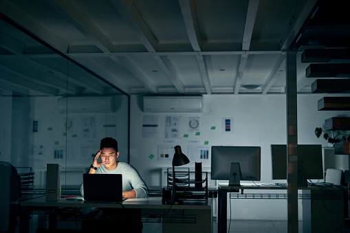 Shot of a young businessman looking stressed during a late night in a modern office