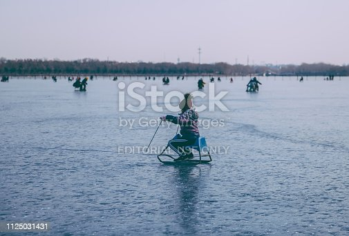 Beijing, China - January 26th, 2019: Beijingers are enjoying a day of lake skating at the frozen lake of the Summer Palace. Summer Palace is one of the most popular tourist attractions in Beijing.