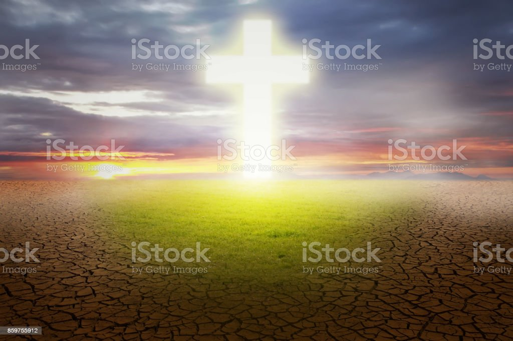 When the Christian cross gave the grass in the barren land, against the background of the sunset stock photo