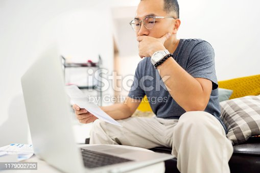Taiwanese ethnicity man looking at his financial situation on his laptop and holding bills in his hand.
