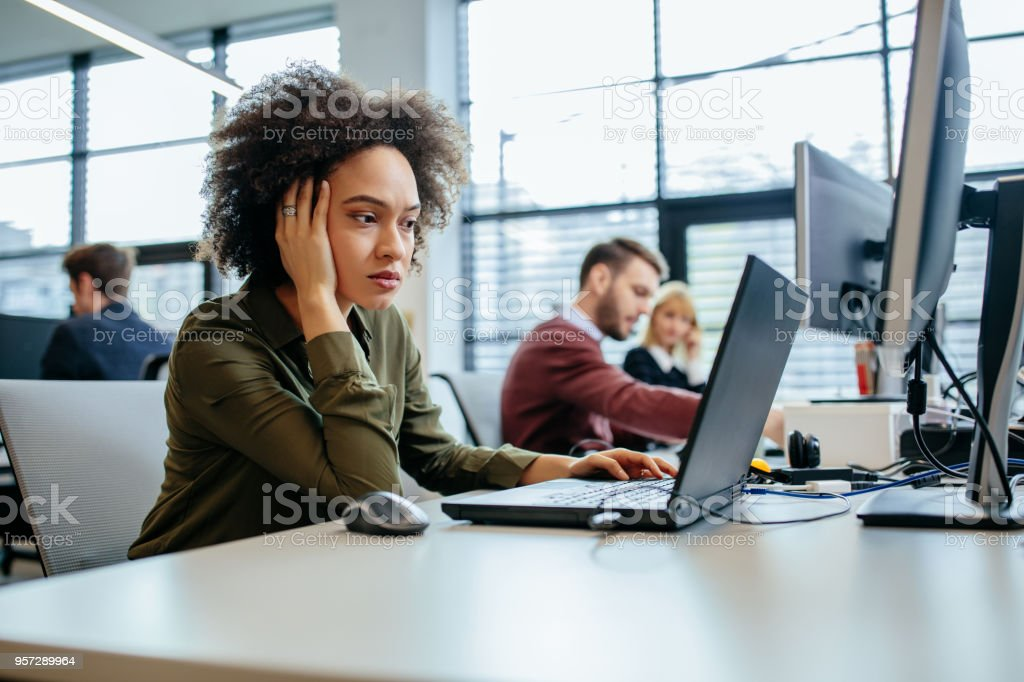 When the numbers don't add up Cropped shot of a exhausted businesswoman sitting in front of her computer in an office Adult Stock Photo