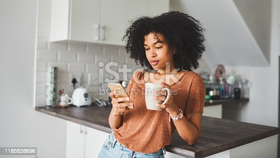 Shot of a young woman using a smartphone and having coffee in the kitchen at home