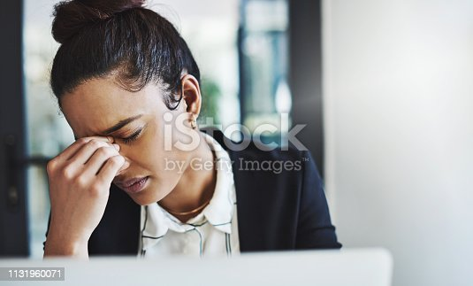 Shot of a young businesswoman looking stressed while working at her desk in a modern office