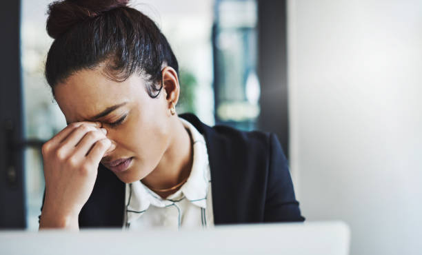 When the workday gets the better of you Shot of a young businesswoman looking stressed while working at her desk in a modern office mistake stock pictures, royalty-free photos & images