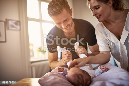 Shot of a happy young couple bonding with their baby girl at home
