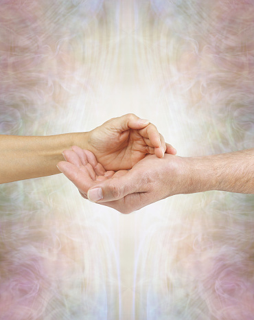 female hand laying on male hand against a subtle golden ethereal energy field with copy space