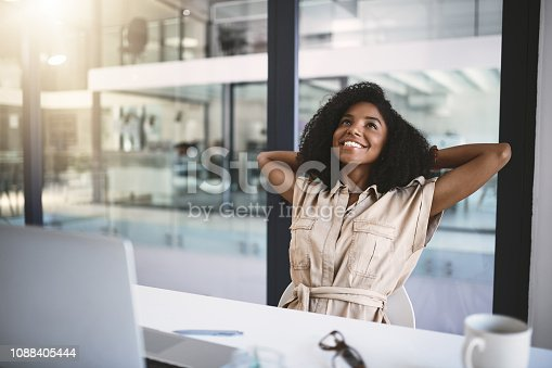 Shot of a happy young businesswoman relaxing at her desk in a modern office
