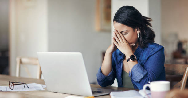 When working from home isn't work out Shot of a young woman looking stressed while using a laptop to work from home mistake stock pictures, royalty-free photos & images